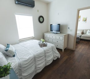 A model apartment at one of our assisted living facilities including a bedroom with white bed, bedding, and dresser, and a doorway leading to a living room in the background.