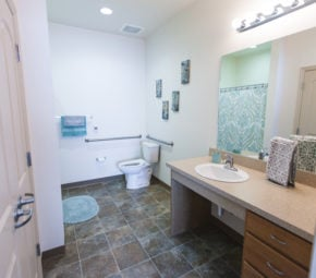 A model bathroom with countertop, tile flooring, and porcelain toilet in the background.