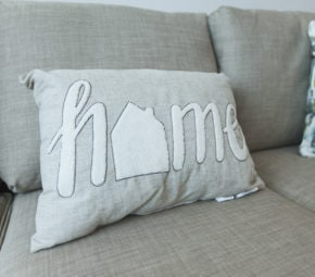 "A gray pillow with ""home"" sewn on it, sitting on a gray couch."