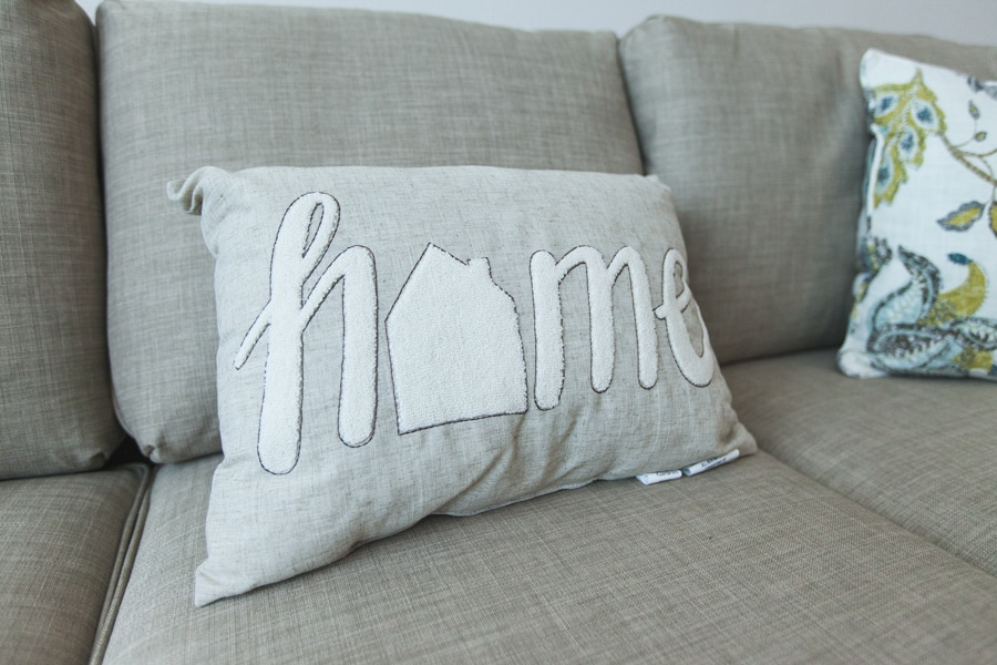 """A gray pillow with """"home"""" sewn on it, sitting on a gray couch."""
