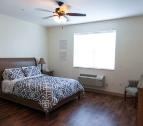 A model bedroom including a wooden bed frame, full-sized bed, television, and personal air conditioning unit.
