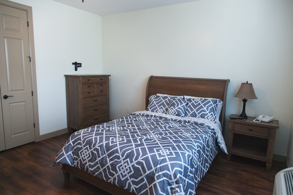 A model bedroom with a full sized bed with wooden dresser and nightstand, plus a lamp and telephone.