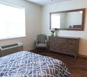 A model bedroom including a bed, wooden dresser, air conditioning unit, mirror, and chair.
