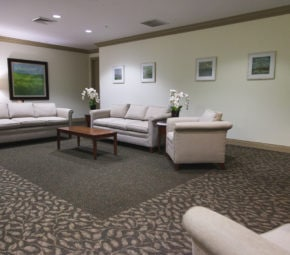 A lounge area at our ALF in South Tampa, including two beige couches, a brown coffee table, two beige chairs, and multiple portraits.