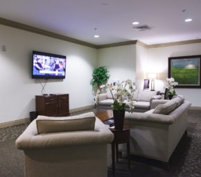 The lounge area at one of our assisted living communities, featuring a television, multiple couches and chairs, lamps, flowers, and other decorations.