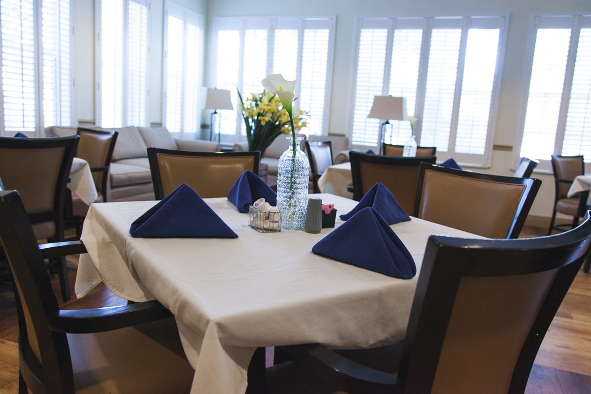A setting including chairs, napkins, and a floral centerpiece at one of our ALFs in Tampa.