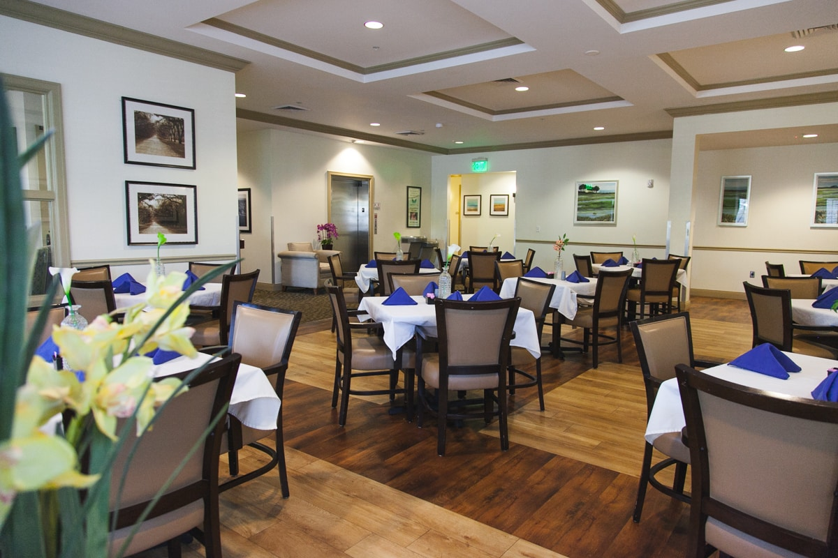 The dining room at Angels Senior Living at South Tampa featuring multiple tables with four chairs, with our entryway and elevator in the background.