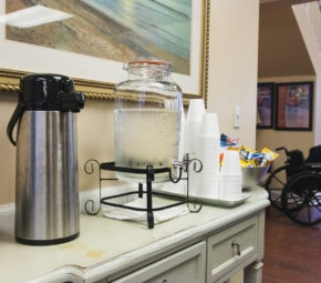 A table with a dispenser of ice cold water, coffee carafe, cups, and snacks with a resident in the background at one of our assisted living facilities.