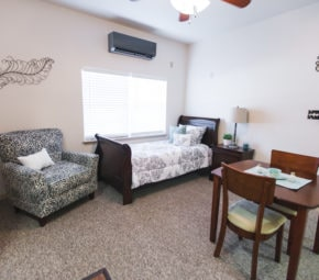 A model bedroom at Angels Senior Living at New Tampa including a comfortable chair, a bed and wooden frame, and wooden dining table.