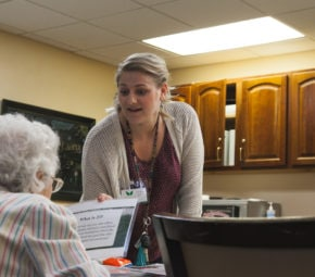 An employee and resident look over printed materials in one of our South Tampa ALF's living spaces.