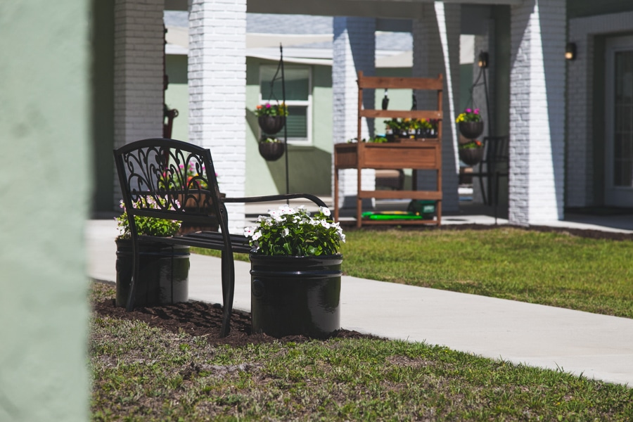 Black bench with large black flower pots on either side in spacious courtyard at our New Port Richey location.