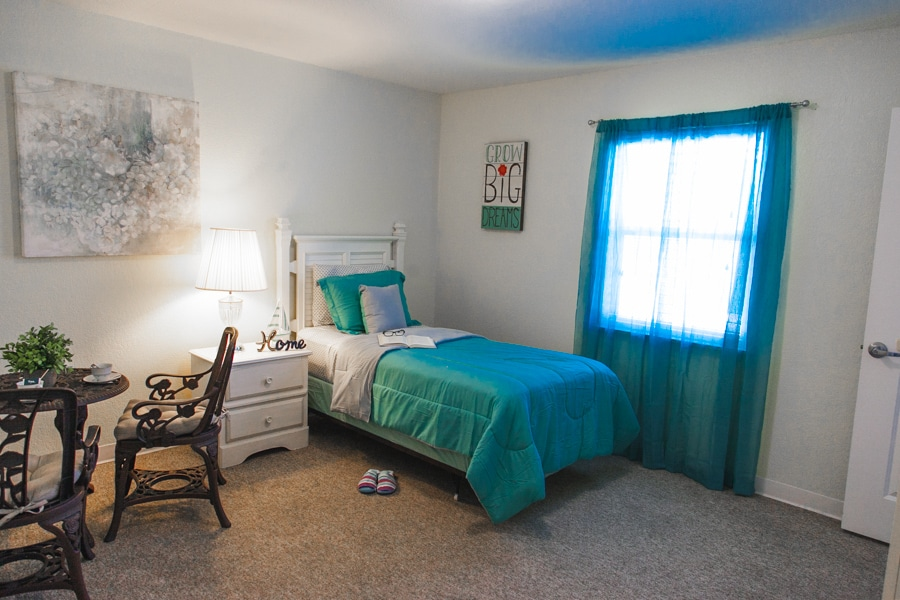 A model bedroom at our New Port Richey assisted living facility including bed with blue and white covers and pillowcases, blue curtains, and blue and white decorations.