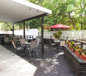 The patio of our South Tampa assisted living facility, including plants, chairs, an umbrella, and overhang.