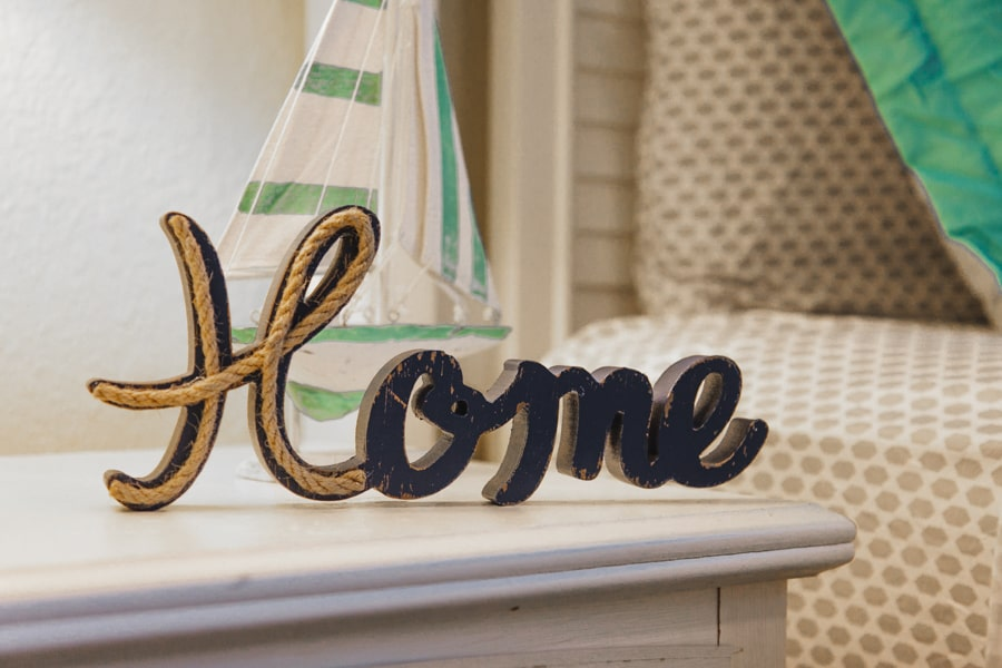 """Wooden carved sign reading """"Home"""" with sailboat in the background on top of cream wooden dresser next to bed."""