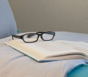 Black glasses and a book with blue cover on a bed with blue cover.