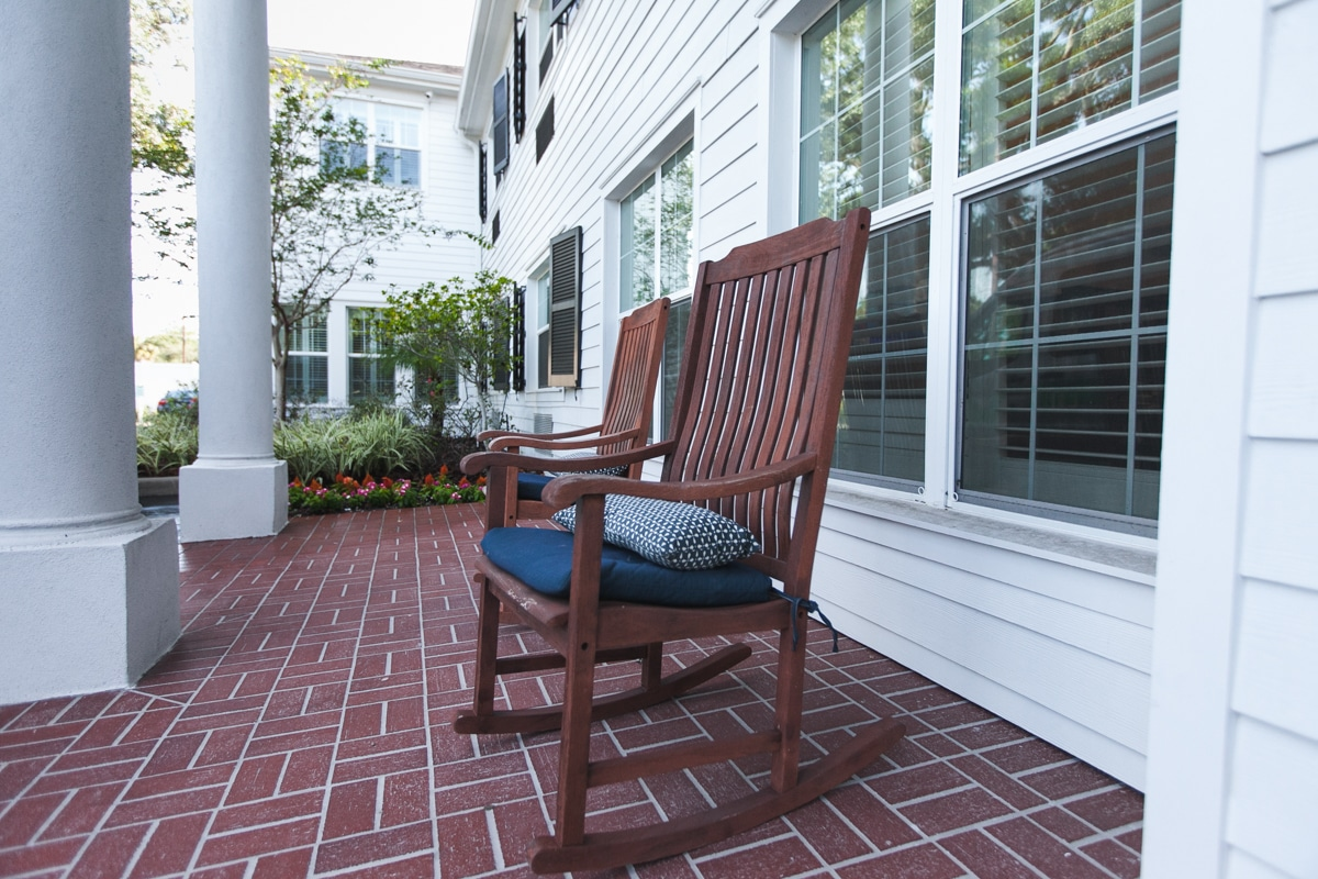 A closeup of two red wood patio rocking chairs on the patio of our South Tampa assisted living community.