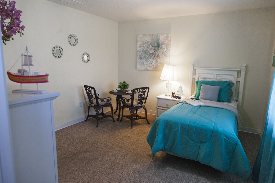Model beach-style bedroom including full bed with blue covers and pillow cases, black table and chairs in the background.