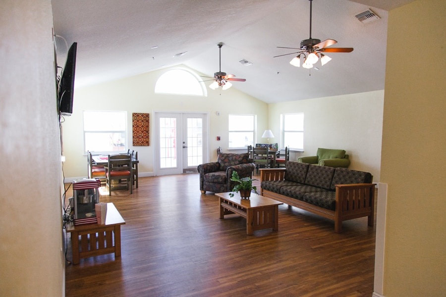 Wooden floored room with three windows and white double doors, including a domed window near the roof, one brown couch, a brown chair, two tables with board games, a coffee table, and television.