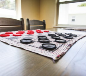 Wooden table and chairs with checkers mat and set laid out at our New Port Richey assisted living facility.