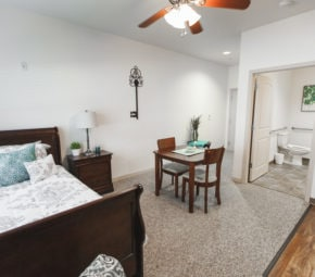 A model bedroom at Angels Senior Living at New Tampa including wood flooring, a bed and wooden frame, and wooden dining table.