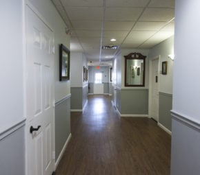 Main hallway of our Palma Ceia memory care facility including multiple resident doors and a secured exterior door at the end of the hall.