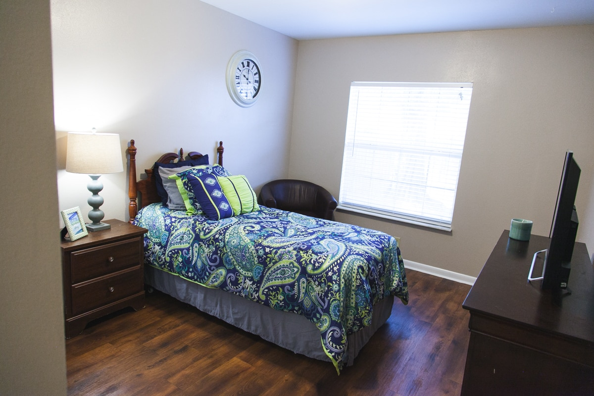 Sea-themed model bedroom at our Palma Ceia memory care facility including bed with blue and green covers, wooden furniture, and large analog clock.
