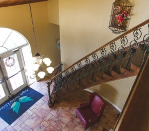 Aerial view of tiled reception area and brown wooden and iron wrought staircase at our Palm Harbor ALF.