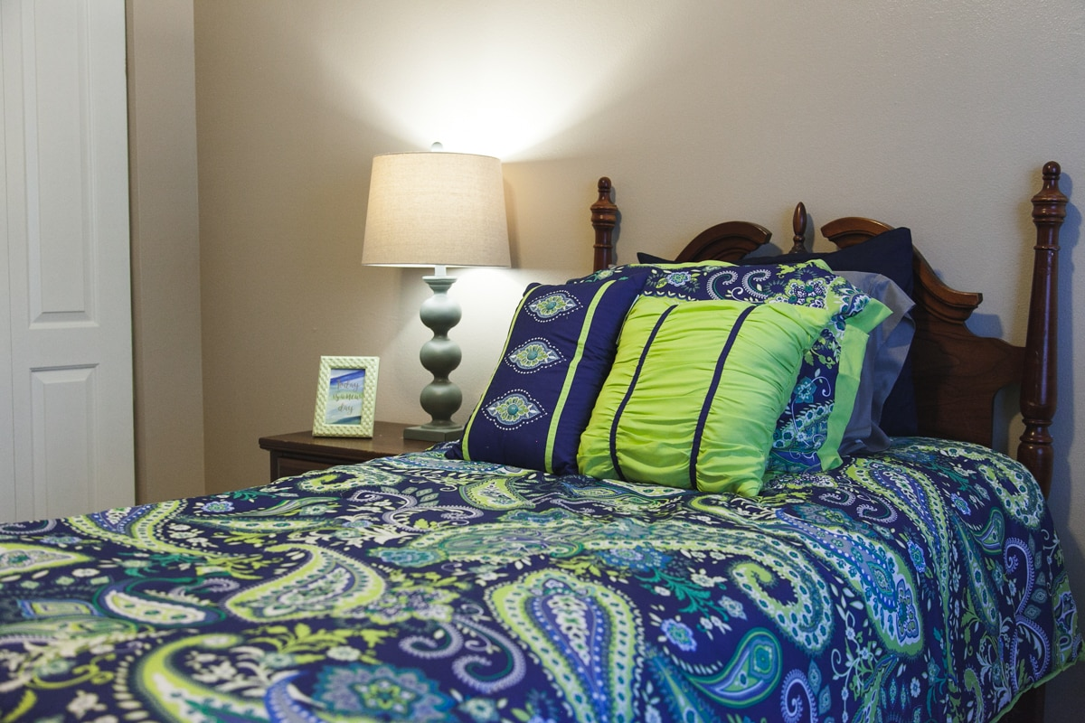 A closeup of a sea-themed model bed and pillows with blue and green covers.