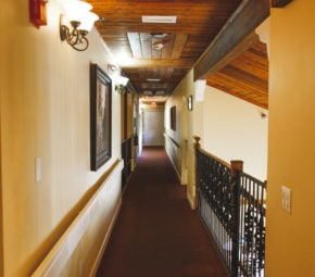Well-lit second floor hallway with brown carpet, wooden ceiling, and orange walls at our Palm Harbor ALF.