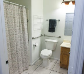 Model bathroom with curbless shower for seniors, including pink and black floral shower curtain, porcelain toilet, and black towels.