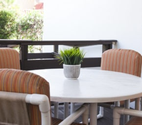 Circular, white patio table with four orange and brown patio chairs and a centerpiece with greenery at our memory care community in Palma Ceia, Florida.