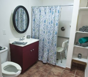 Palm Harbor ALF model bathroom with porcelain toilet, green and gray towels, wooden vanity, round black mirror, and low curb shower with blue, green, and grey shower curtain.