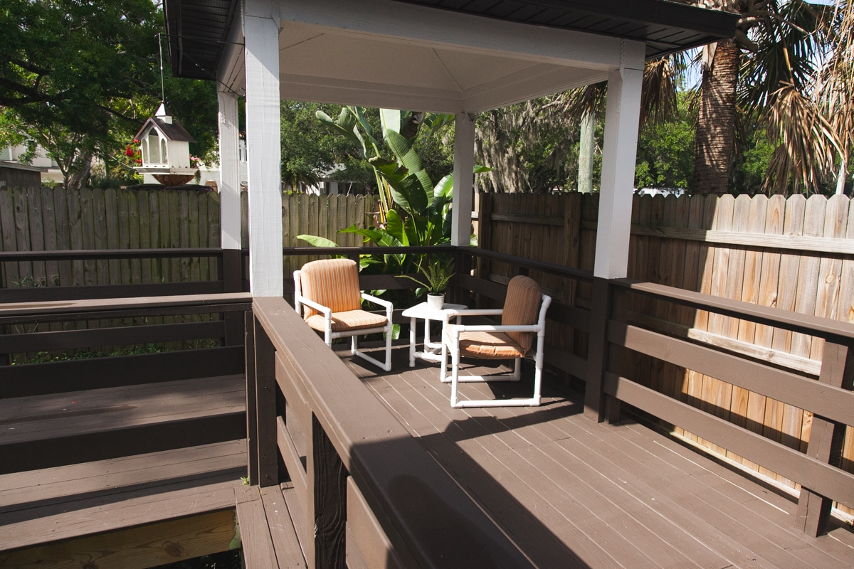 Sunny outside deck area including a gazebo top, two orange and brown chairs, and a white table at our Palma Ceia memory care community.