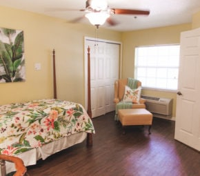 Model bedroom with wooden bed frame, bed with floral sheets, and orange lounge chair with decorative pillow and blanket.