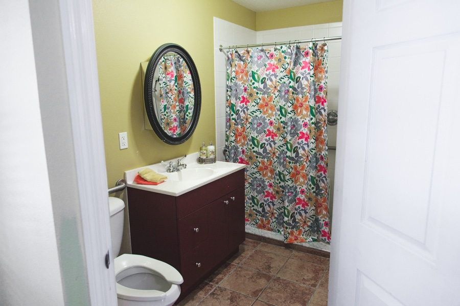 Model bathroom at our Palm Harbor ALF including tiled floors, wooden vanity with black circular mirror, and floral shower curtain concealing low curb shower providing easy entry for seniors.