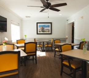 Dining area with wooden tables, orange and black chairs, ceiling fan, and multiple floral centerpieces.