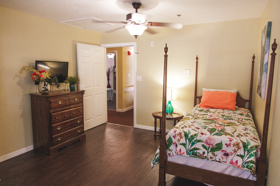 A model bedroom at our Palm Harbor ALF including a bed with wooden bed frame, floral sheets, and a dresser with floral decoration.