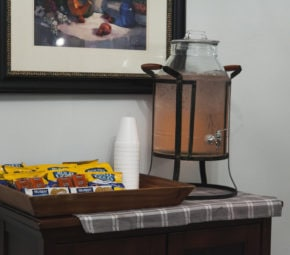 Snack area at one of our memory care facilities offering a glass water dispenser, pretzels, crackers, and cookies.