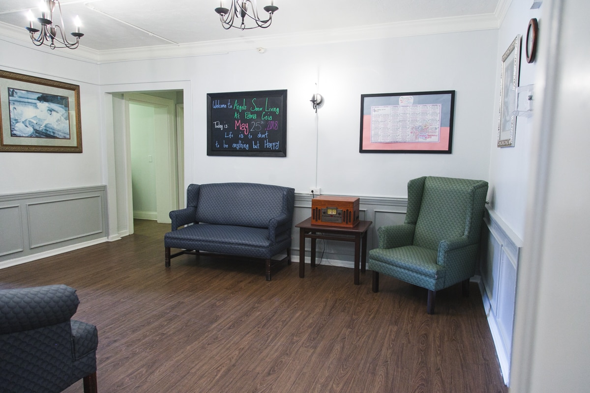 Sitting area with blue loveseats and green chair, copy of monthly schedule, chalkboard, and portraits.