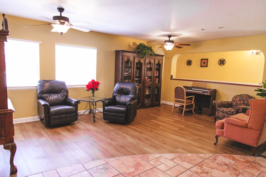 Living room area at our Palm Harbor ALF, including two brown leather chairs, bookcase, floral chair, orange chair, and piano.
