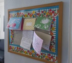Board with floral and picket fence paper with several thank you cards attached to it.