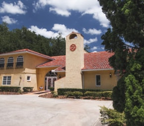 Mediterranean-style bed and breakfast view of our Palm Harbor ALF, including orange painted exterior and red brick roofing with white doors and windows on the first and second floors.