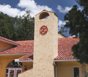 Exterior closeup of our Palm Harbor assisted living facility, formerly known as Rose Garden, with red brick roofing and orange paint.