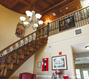 Entrance and wooden staircase leading to second floor with chandelier, multiple other lights, fire alarm control panel, and other decorations.