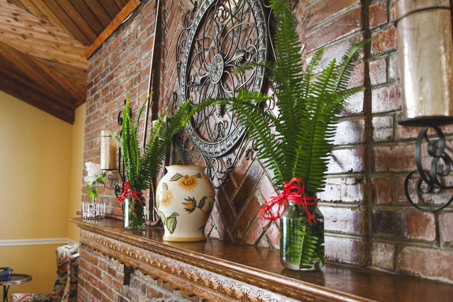 A shelving unit with a floral vase, two mason jars with ferns inside, and other decorations at our Palm Harbor assisted living facility.