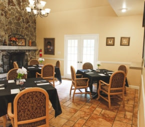 Dining room with tiled flooring, three black linen tables set for four with floral centerpieces, brown and red chairs, a fireplace, and decorations on the walls.