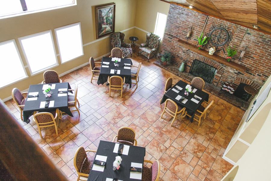 Dining room seen from second story with tiled flooring, red and brown wooden chairs, and wooden tables with black table liners and floral centerpieces set for four.