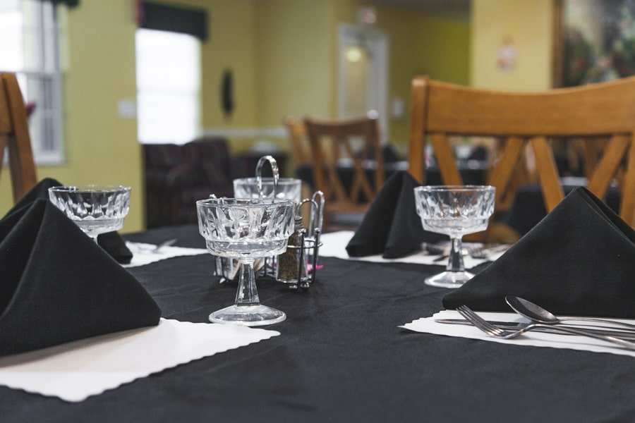 Table with black linen and settings with crystal drinking glasses.