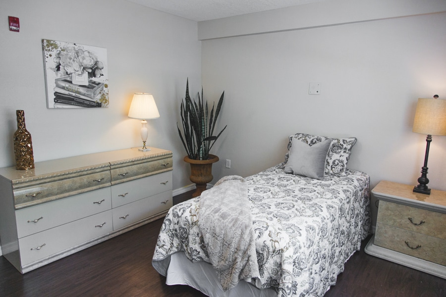 Model bedroom with granite nightstand and white and granite dresser, bed with black and white sheets.