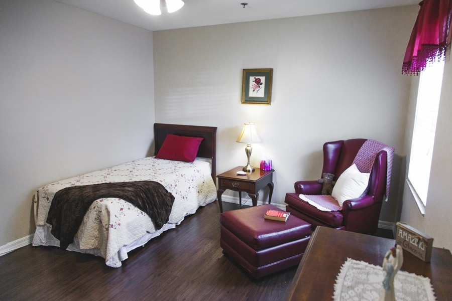 Model bedroom with brown wood flooring, white sheeted bed, red pillow, and red lounge chair with brown nightstand in background.